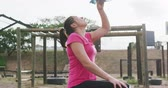 engel : Side view of an exhausted mixed race woman wearing a pink t shirt at boot camp, sitting and pouring water from a bottle on her face and refreshing herself after training, with a climbing frame in the background, in slow motion