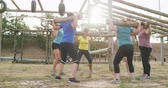 проведение : Side view of a happy multi-ethnic group of female friends enjoying exercising at boot camp together, standing in a circle doing squats with wooden poles on their shoulders, in slow motion