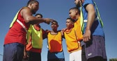 amontoado : Low angle front view of a multi-ethnic group of male football players wearing sportswear and coloured bibs, training at a sports field in the sun, standing in huddle, talking, motivating, in slow motion