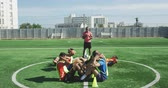 ups : Side view of a multi-ethnic group of male soccer players wearing sportswear and coloured bibs, training at a sports field in the sun, doing sit ups in a row, their coach standing in the background, in slow motion