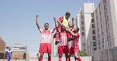 omuz : Front view of a multi-ethnic group of male football players wearing a team strip, training at a sports field in the sun, holding one of their teammates on the shoulders, celebrating scoring a goal in slow motion Stok Video
