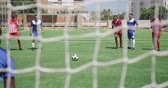 trest : Front view of a multi-ethnic group of male football players wearing a team strip, training at a sports field in the sun, playing a match, executing a penalty kick, seen through goal net in slow motion Dostupné videozáznamy
