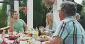 középkorú : Side view of a multi-generation Caucasian family enjoying their time together in a garden, sitting by a table, talking, gesturing in slow motion Stock mozgókép