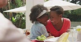 középkorú : Front view of an African American girl having a good time with her family, sitting by a table in a garden, whispering something into her mother ear, laughing, on a sunny day, in slow motion