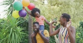omuz : Side view of an African American family having a good time in a garden, running and jumping, a girl is sitting on her father shoulders, holding balloons, on a sunny day, in slow motion