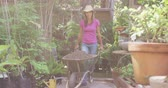 kruiwagen : Front view of a Caucasian woman, enjoying time in a sunny garden, wearing a straw hat, a purple t shirt and blue jeans, pushing a wheelbarrow filled with earth, in slow motion