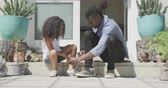 enjoying : Side view of an African American man and his mixed race daughter enjoying time in front of the house together, a man is tying his daughters shoe, in slow motion