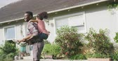 vader : Front view of an African American man and his mixed race daughter enjoying time at a garden together, a man is carrying his daughter piggy back, spinning, pointing in the air,  in slow motion
