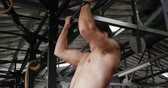 középkorú : Side view close up of a shirtless athletic Caucasian man cross training at a gym, doing chin ups holding onto a bar Stock mozgókép
