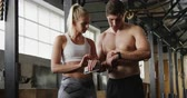 középkorú : Front view of a shirtless athletic Caucasian man and a woman wearing sports clothes cross training at a gym, standing, talking, checking their watches and smartphone, smiling and giving each other a high five between exercises