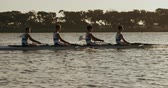 meydan okuma : Side view of four Caucasian male rowers, during a rowing practice, sitting in a boat, rowing, during a sunset, in slow motion Stok Video