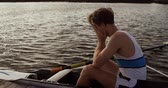 hombre adulto : Side view of a Caucasian male rower, after a rowing practise, sitting in a boat by a jetty, hiding his face in his hands, on a sunny day, in slow motion