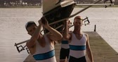 hombre adulto : Side view close up of four Caucasian male rowers, standing in a row on a jetty, holding a boat above their heads bottom up, putting it on their shoulders, during a sunset, in slow motion