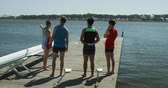meydan okuma : Side view of four Caucasian male rowers, standing on a jetty, holding oars, talking and discussing, one man is pointing on something on a lake, on a sunny day, in slow motion Stok Video