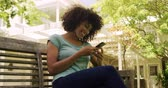 telemóvel : Front view of a mixed race woman enjoying her time in a garden, sitting on a bench, using a smartphone and smiling, on a sunny day, in slow motion. Social distancing and self isolation in quarantine lockdown