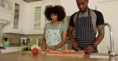 középkorú : Front view of a mixed race couple enjoying their time together in an apartment, standing in a kitchen, wearing cooking aprons, cooking, cutting vegetables, in slow motion. Social distancing and self isolation in quarantine lockdown