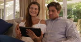 hombre adulto : Front view close up of a Caucasian couple enjoying their time together in an apartment, sitting on a couch, a woman is holding a digital tablet and is pointing at it, smiling, in slow motion Archivo de Video