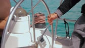 námořník : Man controls the steering wheel of a sailing boat. Closeup on his hand. Dostupné videozáznamy
