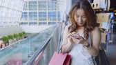 gönderme : Woman Using Cellphone And Holding Shopping Bags In Shopping Mall