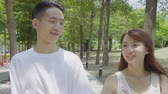 разговор : Young Asian Couple In The Park Стоковые видеозаписи