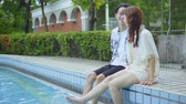 amor : Couple Sitting By The Pool Kicking Water