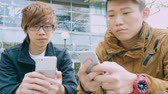 discagem : Two Man Playing Smart Phones Stock Footage