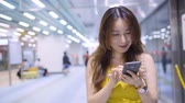 смс : Pretty Asian Woman Using Smart Phone At Subway Station