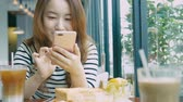 tapping : Young Woman Using Smart Phone At Coffee Shop Stock Footage