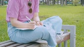 Asian Female Student Writing Notes In The Park