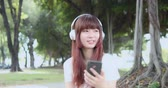 earbuds : Young Asian Woman Listen To Music With Earphone And Her Smart Phone Stock Footage
