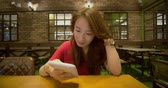 Asian Woman Using Smart Phone At Coffee Shop Archivo de Video