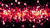 Background with shiny red particles. Beautiful bokeh light background. Red confetti shimmering with magical sparkling light. Seamless loop Stockvideo