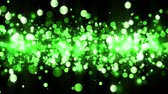 Background with shiny green particles. Beautiful bokeh light background. Green confetti shimmering with magical sparkling light. Seamless loop Stockvideo