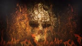 ksi����yc : Ancient Skull Wall in Hell 4K Loop features an old wall with a skull face carved into the rock with flames coming up from beneath