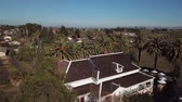 Aerial. beautiful big house in the middle of a field surrounded by palm trees 動画素材
