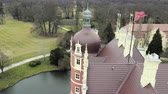 barok : View from tower on the roof of a classicist castle with red facade. Monumental palace with moat, sculptural decoration