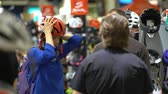 headpiece : HELSINKI, FINLAND - MARCH 17, 2017: Buyers choose Bicycle helmets in the store. All for active lifestyle, outdoor activities and versatile sport at the international fair GOEXPO 2017 in the expocenter Messukeskus.