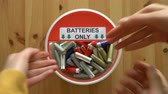 utilization : Many hands putting lot of used batteries in the recycling box. Top view. Close up Stock Footage