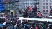 remonstrance : KIEV, UKRAINE - JANUARY 20, 2014: Several journalists with cameras standing on the broken bus among the crowd of protesters during clashes in Kiev on the street Grushevskogo.