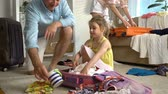 paketlenmiş : Happy little girl with her parents is carefully packing a luggage for a new journey. Slow Motion.