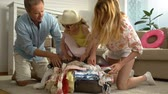 embalado : A Young Family with Child Trying to Close the Chock-full Suitcase. Slow motion