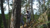 me : Elderly active couple climbing on the rock in the northern forest. Scandinavian landscape with cliffs, pine trees and moss.