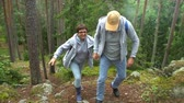 альпинист : Elderly active couple climbing on the rock in the northern forest. Scandinavian landscape with cliffs, pine trees and moss. Slow motion