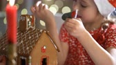 glaze : Young mother and adorable daughter in red hat building gingerbread house together. Beautiful decorated room with lights and Christmas tree, table with candles and lanterns. Happy family celebrating holiday.