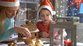 keks : Young mother and adorable daughter in red hat building gingerbread house together. Beautiful decorated room with lights and Christmas tree, table with candles and lanterns. Happy family celebrating holiday.