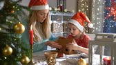 ジンジャーブレッド : Young mother and adorable daughter in red hat building gingerbread house together. Beautiful decorated room with lights and Christmas tree, table with candles and lanterns. Happy family celebrating ho 動画素材