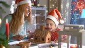 icings : Young mom and cute child in red hat building gingerbread house together. Girl licking glaze off. Beautiful decorated room with lights and Christmas tree, candles and lanterns. Happy family celebrating. Slow Motion