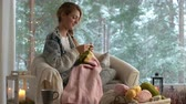 socks : Cozy winter lifestyle. Young woman knitting warm wool sweater in the sitting room against snow landscape from outside. Stock Footage