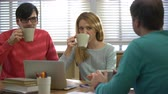 tea time : Coffee-break. An attractive young woman and two young men drinking coffee and talking in the office.