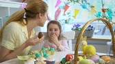 egg painted : Mother And Daughter eating Chocolate Easter Eggs sitting at the holiday table with a basket and a yellow rabbit